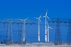 Verschillende windmolens met transmissielijn in de winterlandschap Stock Fotografie