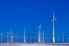 Verschillende windmolens met transmissielijn in de winterlandschap Stock Afbeeldingen
