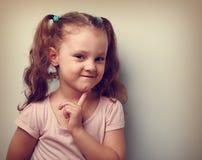 Verschlagenheit, die kleines Kindermädchen mit dem Finger nahe Gesicht denkt Weinlese c Lizenzfreie Stockfotografie