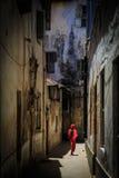 Verschleierte Frau, die durch eine schmale Straße geht Stockbild
