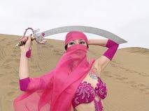 Verschleierte Frau und Säbel an der Wüste Stockfotografie