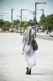 Verschleierte moslemische Frau, die in die Straße nahe der Bahnstation geht stockfotografie