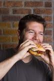Verschlingen eines Hamburgers für das Mittagessen Lizenzfreie Stockfotografie