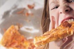 Verschlingende Pizza des Kindes Stockfoto