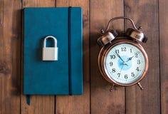 Verschlossen und Schlüssel auf blauem Notizbuch auf hölzernem Hintergrund stockfotografie