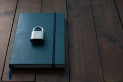 Verschlossen und Schlüssel auf blauem Notizbuch auf hölzernem Hintergrund, private Co lizenzfreie stockfotos