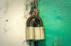 Verschlossenes altes Eisenvorhängeschloß auf einer grünen Tür Stockfotos