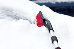 Verschneiter Winter in einer Stadt an einem sonnigen Tag Auto nach Schneefällen im Parkplatz Junge Frau, die versucht, das eisige Lizenzfreies Stockfoto