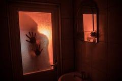 Verschrikkingssilhouet van vrouw in venster Het enge Vage silhouet van Halloween concept van heks in badkamers Selectieve nadruk royalty-vrije stock foto's