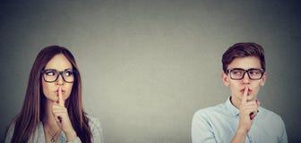 Verschwiegene Leute Junge Frau und der Mann, die einander Stille sagend betrachtet, sind mit dem Finger auf Lippengeste ruhig Stockfoto