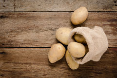 Verse aardappels in de zakken van de hennepzak op rustieke houten achtergrond Ra Stock Foto
