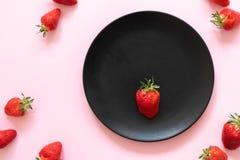 Verse aardbeien één op een zwarte plaat tegen een achtergrond van roze pastelkleur speld-omhoog Royalty-vrije Stock Fotografie