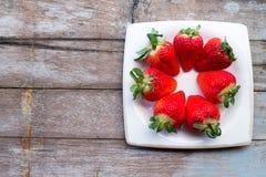 Verse aardbeien in een schotel op houten lijst Royalty-vrije Stock Afbeelding