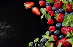 Verse aardbeien, frambozen en bosbessen op een zwarte achtergrond royalty-vrije stock foto's