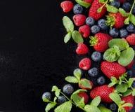 Verse aardbeien, frambozen en bosbessen op een zwarte achtergrond royalty-vrije stock afbeelding