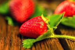 Verse aardbeien met bladeren op houten oppervlakte Stock Foto