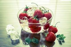 Verse aardbeien met ijsblokjes in de glaskom Stock Afbeeldingen