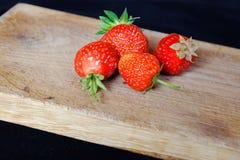 Verse aardbeien op een houten scherpe raad Stock Afbeeldingen