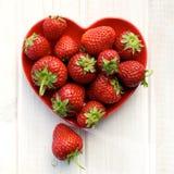 Verse aardbeien op een plaat in de vorm van hart Stock Afbeeldingen