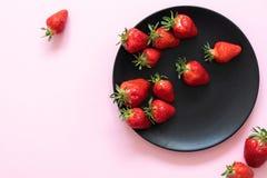Verse aardbeien op een zwarte plaat tegen een achtergrond van roze pastelkleur speld-omhoog Royalty-vrije Stock Foto's