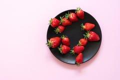 Verse aardbeien op een zwarte plaat tegen een achtergrond van roze pastelkleur speld-omhoog De ruimte van het exemplaar Royalty-vrije Stock Afbeeldingen