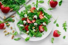 Verse aardbeisalade met feta-kaas, arugula op witte plaat Royalty-vrije Stock Foto