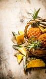 Verse ananassen in de mand Op houten lijst Ondiepe diepte van gebied Stock Fotografie