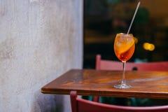 Verse Aperol-geesten coccktail, op houten lijst in restaurant Horizontaal schot van de zomerdrank Oranje vloeistof met ijs Aperet royalty-vrije stock fotografie