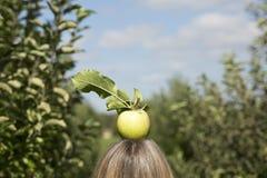 Verse appel bovenop blonde woman& x27; s hoofd Royalty-vrije Stock Fotografie