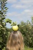 Verse appel bovenop blonde woman& x27; s hoofd Royalty-vrije Stock Afbeeldingen