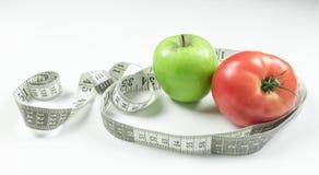 Verse appel met het meten van band Verse tomaat zuur die zuivelproduct op witte achtergrond wordt geïsoleerd stock fotografie