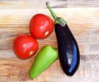 Verse aubergine, tomaten, groene paprika op een houten raad Royalty-vrije Stock Fotografie