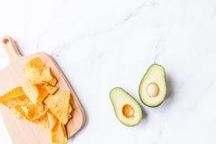 Verse avocado en nachospaanders die op marmeren achtergrond liggen Recept voor Cinco de Mayo-partij De hoogste vlakke mening, luc royalty-vrije stock foto's