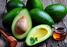 Verse avocado met olijfolie en honing op houten achtergrond Stock Afbeeldingen