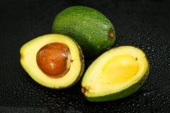 Verse avocado op een zwarte achtergrond met waterdalingen Stock Foto's