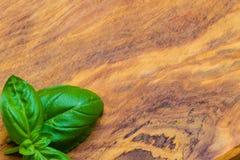 Verse basilicumbladeren op houten lijstachtergrond Stock Afbeelding