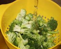Verse besnoeiings organische broccoli in geel vergiet die onder water worden gespoeld royalty-vrije stock afbeelding
