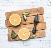 Verse besnoeiingssinaasappelen met bladeren en een houten verbrijzeling voor fruit, op rustiek houten dienblad, hoogste mening stock fotografie