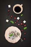 Verse bessen op scherpe cake, kopkoffie, verse Amerikaanse veenbes en suikerkubussen over zwarte achtergrond Hoogste mening Royalty-vrije Stock Foto's