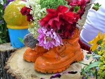 Verse bloemen in een soort het werklaarzen Stock Afbeeldingen