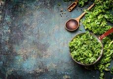 Verse boerenkool in het koken van pot met houten lepel op rustieke achtergrond, hoogste mening, grens Stock Afbeeldingen