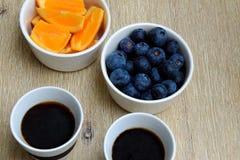 Verse bosbessen, oranje plakken en twee koppen van zwarte koffie stock afbeelding