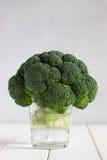 Verse broccoli in glas water op de witte houten lijst Royalty-vrije Stock Foto's