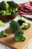 Verse broccoli op scherpe raad met kom, mes en servet Royalty-vrije Stock Foto