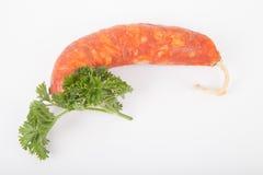 Verse chorizo worst en een twijg van peterselie op een witte backgrou Stock Foto