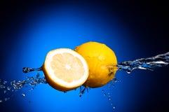 Verse citroen en de helft van citroen in plonsen Stock Foto's