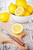 Verse citroenen in een kom en een mes Stock Afbeeldingen