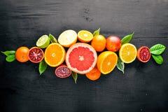 Verse citrusvruchten Citroensinaasappel, mandarijn, kalk Op een zwarte Houten achtergrond Stock Afbeeldingen