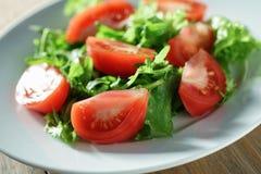 Verse de zomersalade met tomaten, rucola en frillisbladeren in plaat op houten lijst stock afbeeldingen