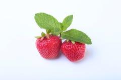 Verse die aardbeien en muntbladeren op witte achtergrond worden geïsoleerd Selectieve nadruk Stock Foto